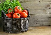 stock photo of wooden basket  - fresh ripe tomatoes in a basket on the table - JPG