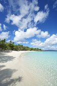 stock photo of deserted island  - Shallow waters lap the shores of deserted Caribbean paradise beach in the Virgin Islands - JPG
