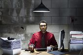 stock photo of basement  - An image of an Indian businessman with a red shirt and tie behind a desk in a basement office - JPG