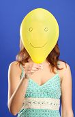 Girl Holding Yellow Smiling Balloon Close Up