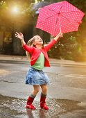 stock photo of boot  - Child with polka dots umbrella wearing red rain boots jumping into a puddle - JPG