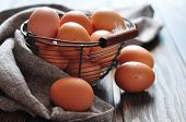 stock photo of wooden basket  - Fresh eggs in a metal basket on wooden background closeup