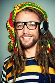 Portrait of a happy rastafarian young man listening to music in headphones.