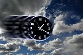 stock photo of time flies  - Detail of blurred speedy clock face with numbers and hands showing time in sky for time flies - JPG
