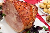 stock photo of smoked ham  - Roasted spiced ham on holiday dinning table garnished with cloves cinnamon sticks hot chili pepper and purple basil. Side dishes and Christmas ornaments around.