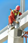 worker in uniform and safety protective equipment at metal construction frames installation and asse