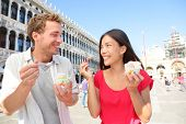 Couple eating ice cream on vacation travel in Venice, Italy. Smiling happy young couple in love havi