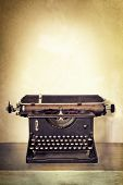 Vintage typewriter on old desk with grunge background.  Lots of copy space.