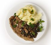Top view of a meal of a fried veal escalope with sauteed mushrooms and mashed potatoes.