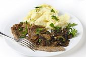 Fried escalope of veal served with mashed potatoes and a creamy mushroom sauce