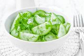 stock photo of cucumbers  - Cucumber salad in a bowl on a table