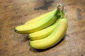 picture of eatables  - Group of four bananas over wood background - JPG