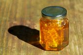 Jar Of Honey With Honeycomb On Wood