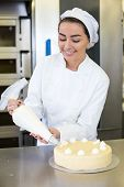 foto of confectioners  - Female baker or confectioner prepares cake with whipped cream