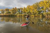 senior male paddler enjoying workout on stand up paddleboard (SUP), calm lake in Colorado, fall colo