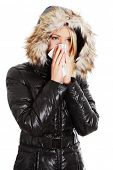 Young woman wearing furry hood, sneezes during cold day. Woman is holding tissue next to her nose.  poster