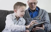 Boy and grandfather on tablet pc