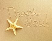 The words Thank You are written on a sand background and the starfish is lying nearby