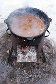 picture of brazier  - food stewed in cauldron on mobile brazier outdoors in winter - JPG