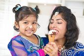 Eating ice-cream. Happy Asian India family sharing ice-cream at home. Beautiful Indian child feeding mother.