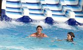 picture of toboggan  - Girl and her grandmother swimming in pool in water park with toboggan in background - JPG