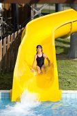 image of toboggan  - Girl with glasses for swimming sliding on toboggan at aqua park - JPG
