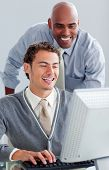 stock photo of business-partner  - Positive business partners working at a computer in the office - JPG