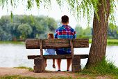 Father And Son Sitting On The Bench Near The Lake