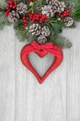 Christmas background border with red heart decoration, holly, mistletoe, fir with snow covered pine