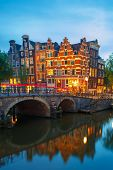 Night City View Of Amsterdam Canal And Bridge