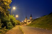 Night landscape with a road leading to the old fortress. Lamplight in the street. Historic Landmark.