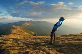 Man balances. Strong wind in the mountains. Autumn Landscape