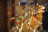 stock photo of church interior  - Burning candles in a Russian orthodox church. Close-up of ordinary church interior. Selective focus. ** Note: Shallow depth of field - JPG