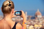 Back side of woman photographing majestic cityscape, Europe, Florence, Italy, Tuscany, travel and tourism concept