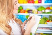 Closeup photo of cute blond housewife writing list to go to supermarket,colorful vegetables and fruits fridge shelves, healthy nutrition concept