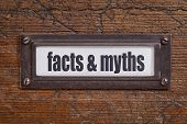 facts and myths  - file cabinet label, bronze holder against grunge and scratched wood