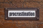 procrastination word - file cabinet label, bronze holder against grunge and scratched wood