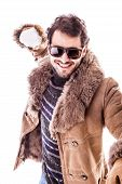 pic of snowball-fight  - a young man wearing a sheepskin coat isolated over a white background playing with a snowball - JPG