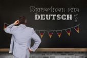 Thinking businessman against blackboard on wall, Do you speak German?