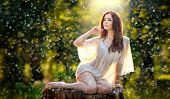 pic of redhead  - Young beautiful red hair woman wearing a transparent white blouse posing on a stump in a green forest - JPG