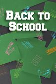 Back to school message against green paper strewn over black