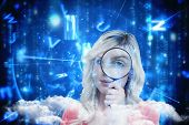 Fair-haired woman looking through a magnifying glass against lines of blue blurred letters falling