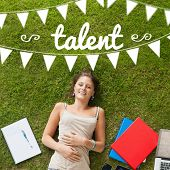 The word talent and bunting against pretty student lying on grass
