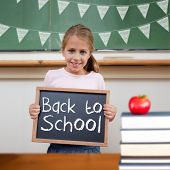 Back to school message against cute pupil showing chalkboard