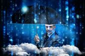 Mature businessman holding an umbrella against lines of blue blurred letters falling