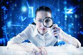 Businesswoman typing and looking through magnifying glass against lines of blue blurred letters fall