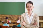 picture of classmates  - Pretty teacher smiling at camera at back of classroom at the elementary school - JPG