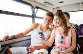 friendship, summer vacation, transport, technology and people concept - smiling couple with smartphone traveling by bus and making selfie