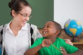Cute pupil and teacher smiling at each other in classroom at the elementary school