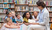 stock photo of pupils  - Cute pupils and teacher reading in library at the elementary school - JPG
